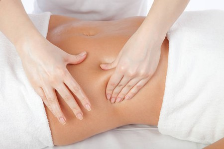 Beautiful girl having stomach massage. Body care concept in studio